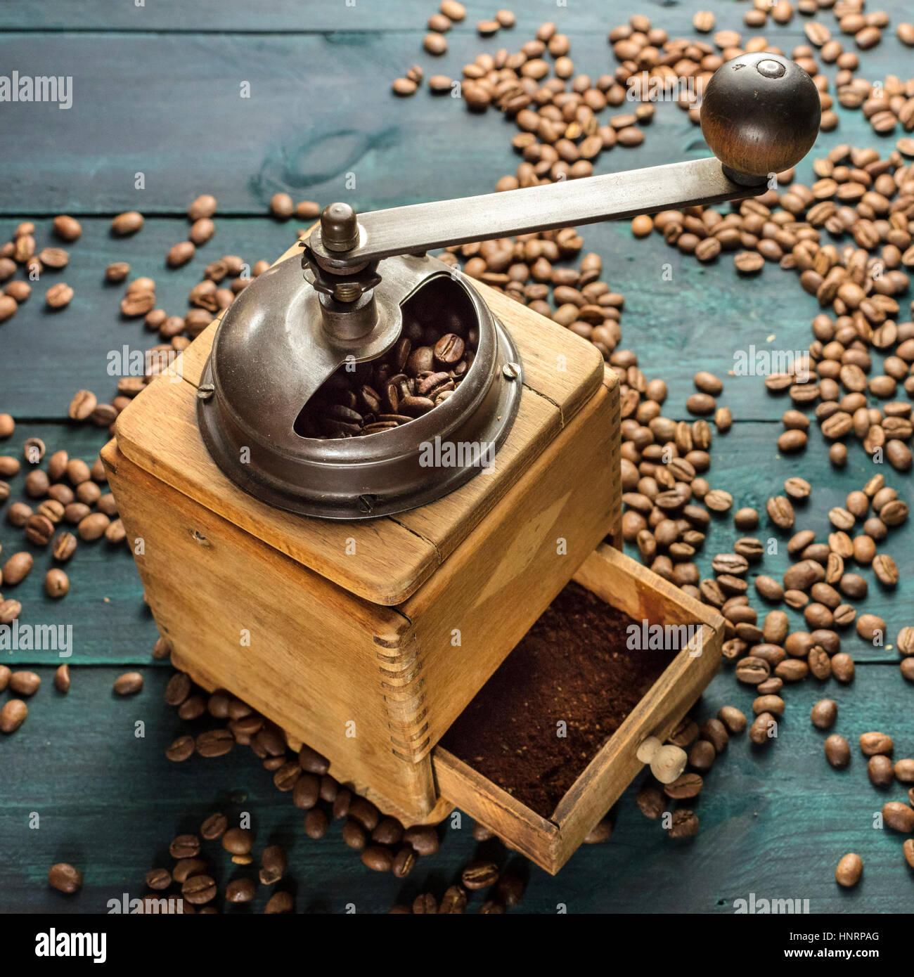Vintage macinino da caffè con fagioli sparsi intorno Immagini Stock