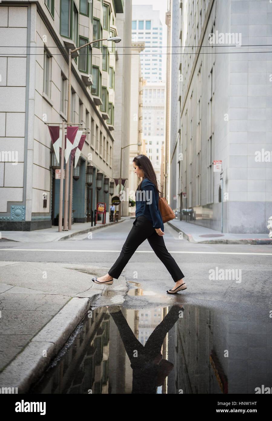 La riflessione in una pozza di cinesi imprenditrice attraversando via Foto Stock