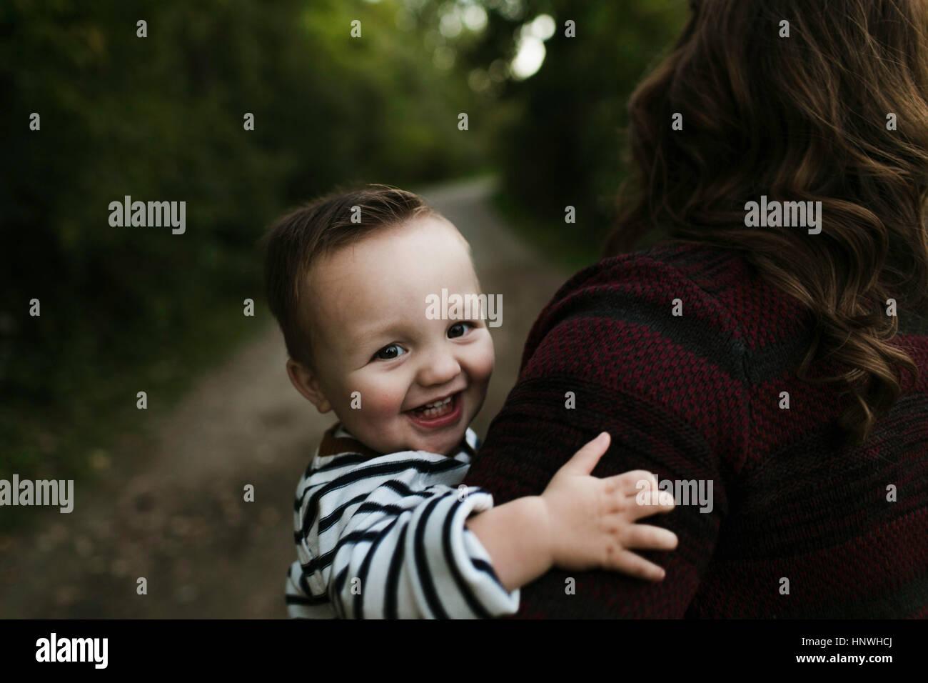 Baby boy in madre di braccia guardando sorridente della fotocamera Immagini Stock