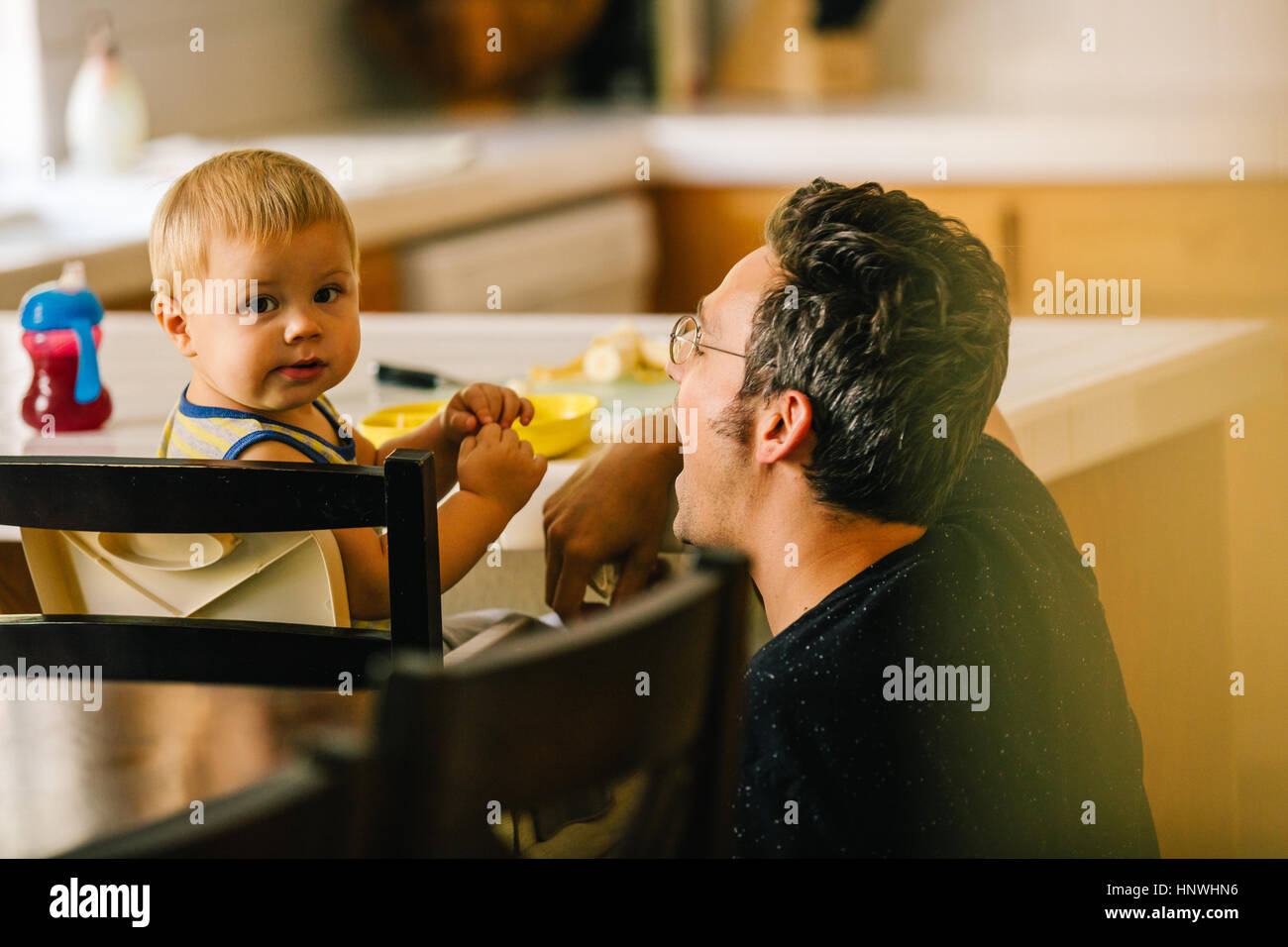 Padre aiutando i giovani figlio all'ora dei pasti Immagini Stock