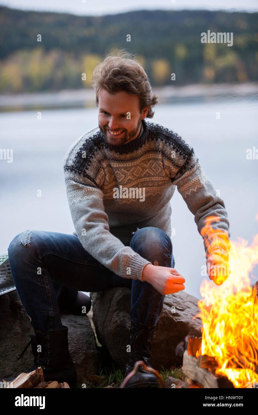 Riscaldamento man mano da falò sulla camping sul lago Immagini Stock