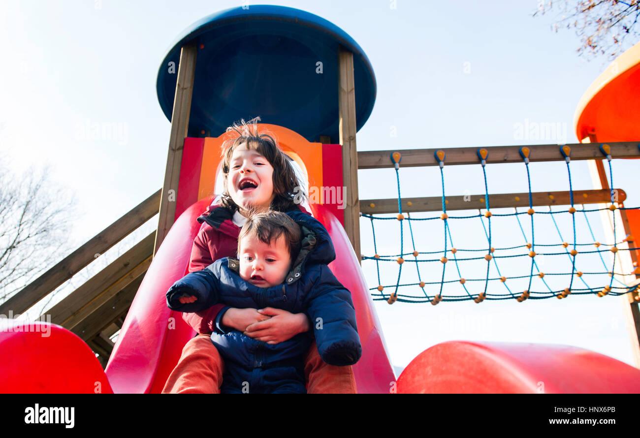Ragazzo e baby fratello lo scorrimento verso il basso il parco giochi slitta Immagini Stock