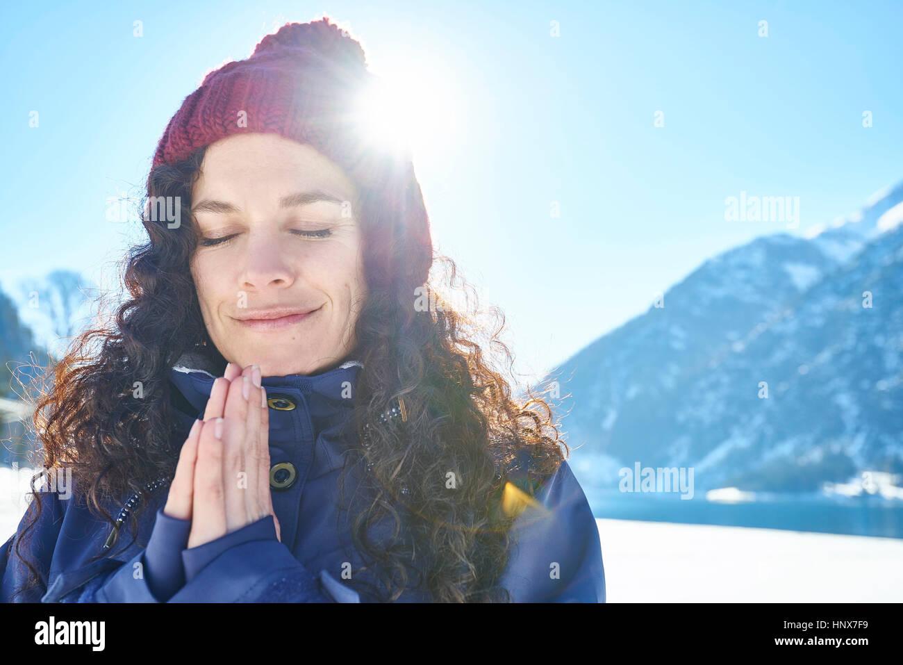 Ritratto di donna in knit hat a praticare yoga e meditazione in coperta di neve paesaggio soleggiato, Austria Immagini Stock