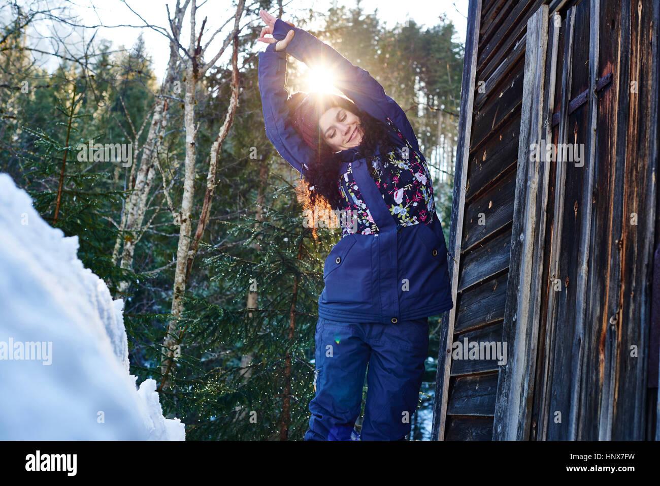 Donna in abbigliamento invernale praticare Half moon yoga posa in neve tramite log cabin, Austria Immagini Stock