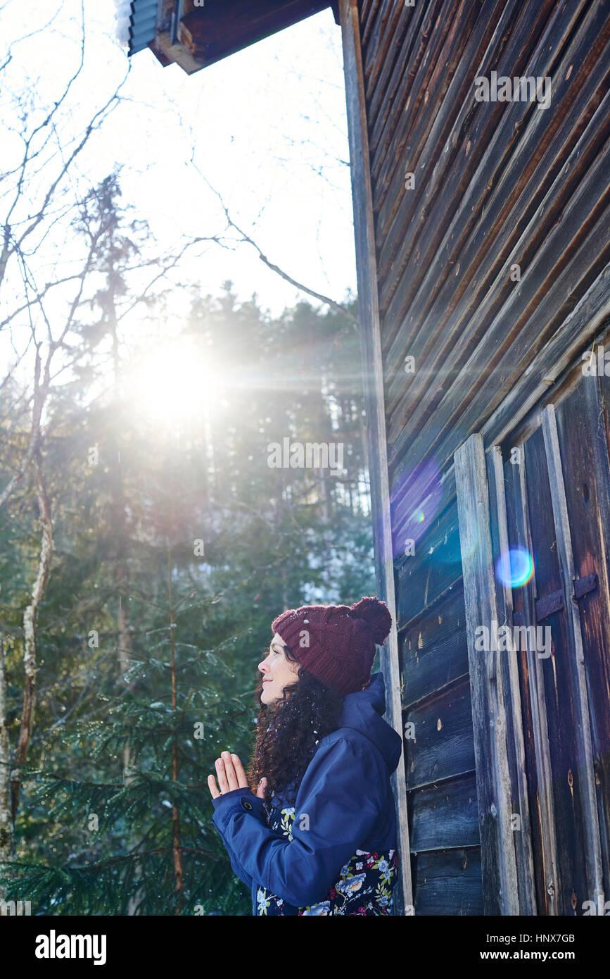 Donna in knit hat a praticare yoga e meditazione da log cabin Immagini Stock