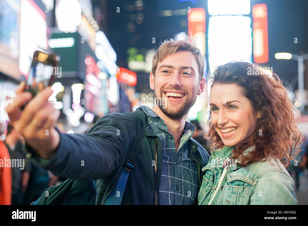 Coppia giovane tenendo selfie in Times Square a New York City, New York, Stati Uniti d'America Immagini Stock