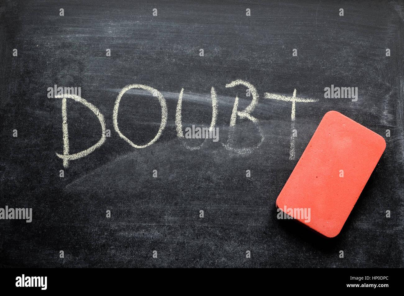 Cancellazione di dubbio, mano parola scritta sulla lavagna cancellata concept Immagini Stock