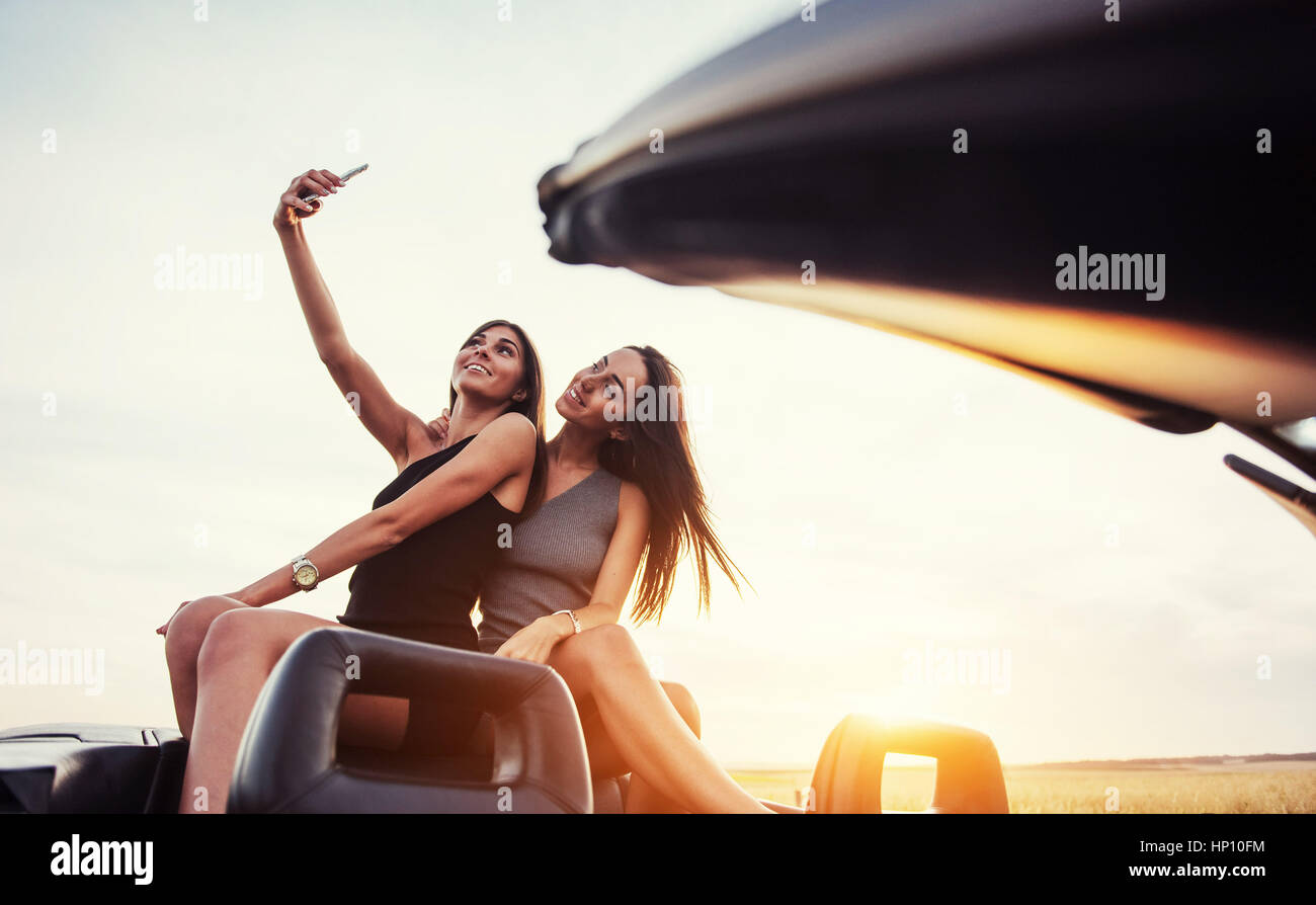 Due giovani donne a scattare una foto. Le ragazze che posano volentieri Immagini Stock