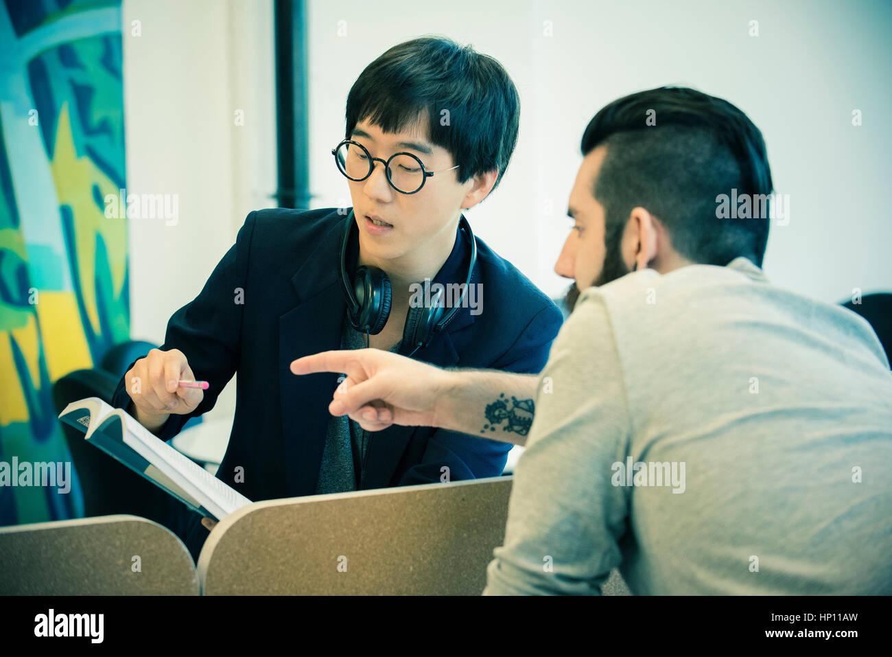 Gli uomini a discutere di libro insieme Immagini Stock