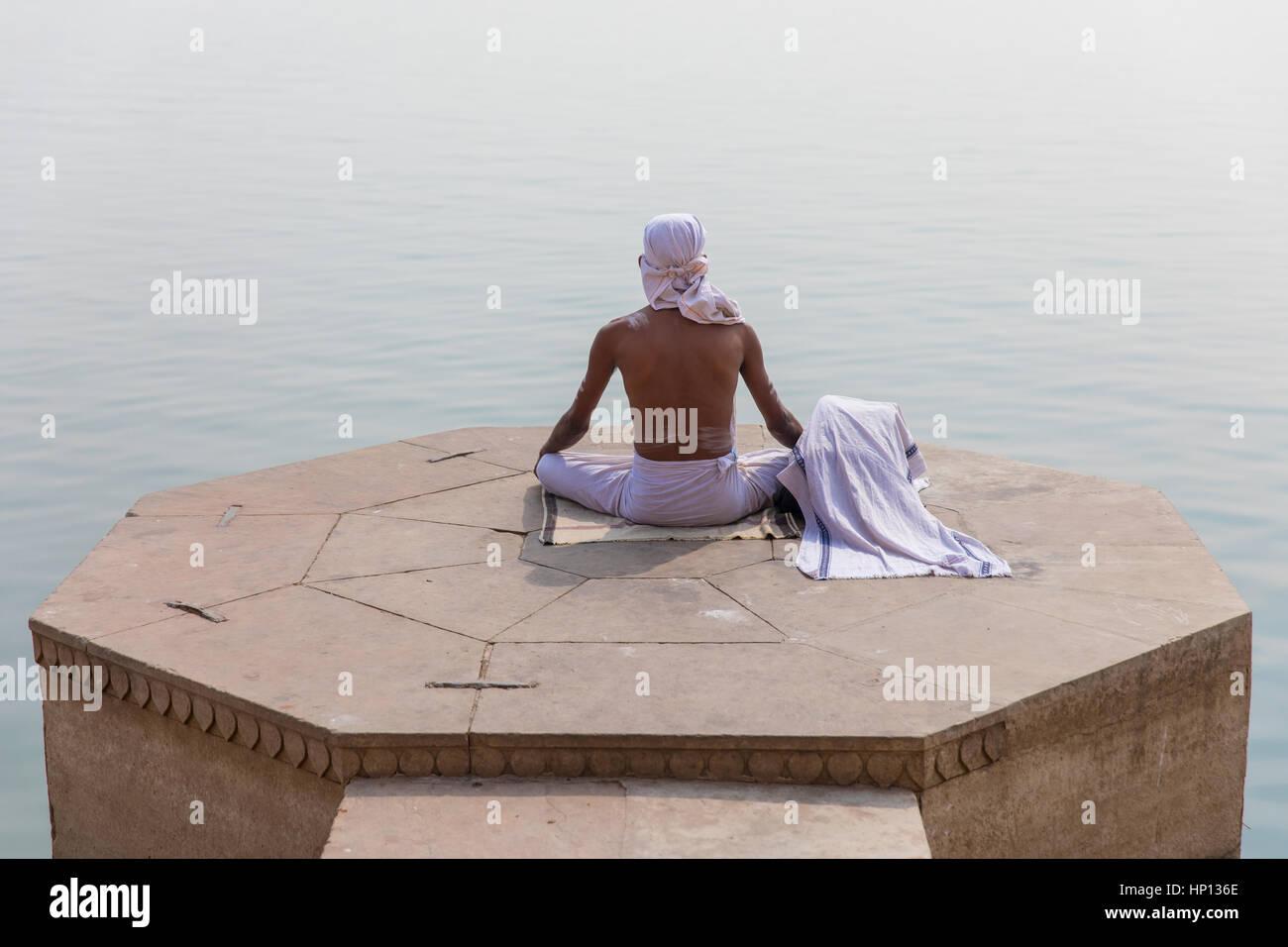 Un uomo medita sul Fiume Gange a Varanasi, uno di India del santissimo città. Varanasi è una destinazione Immagini Stock