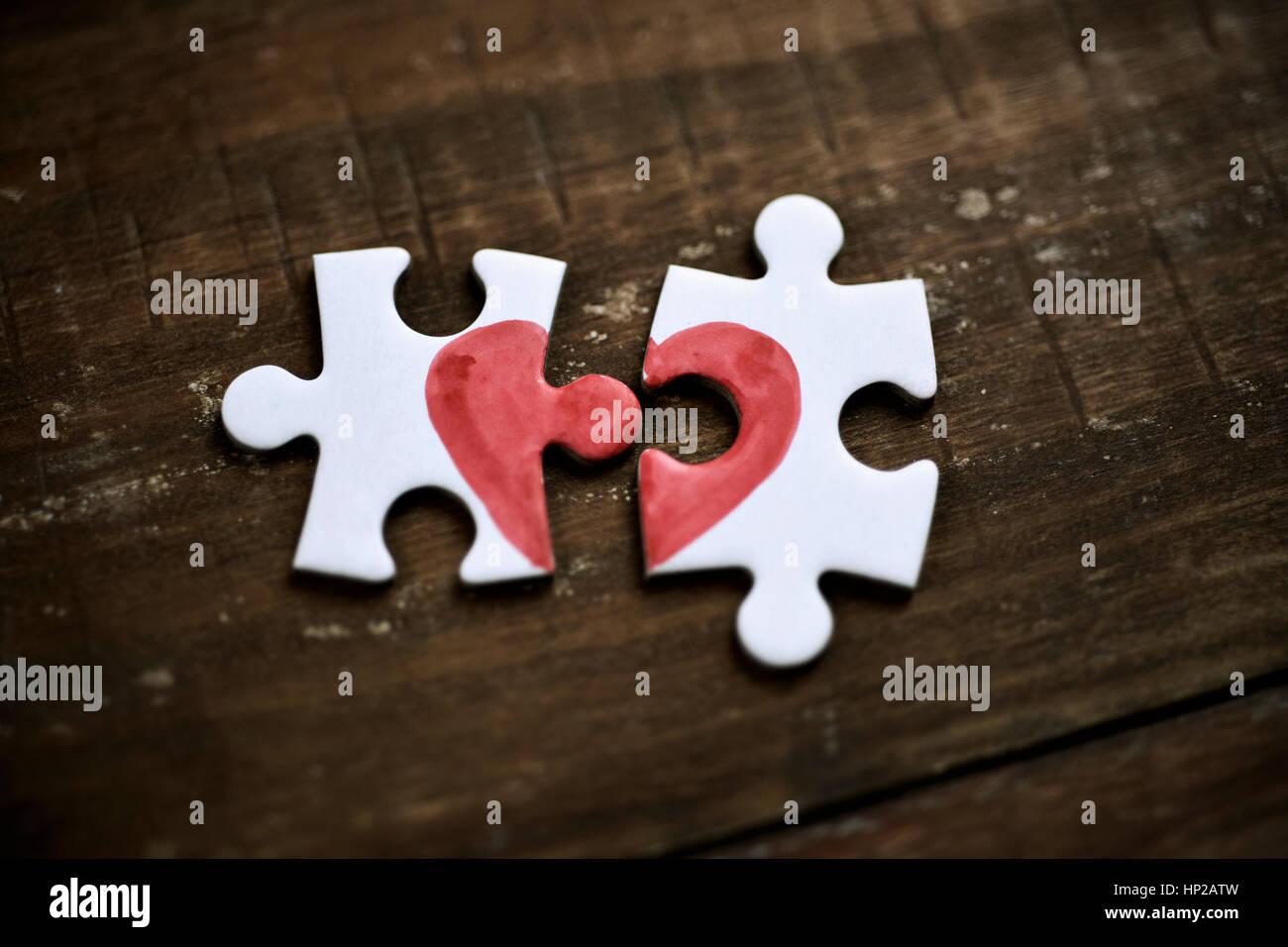 Primo piano di due separate di pezzi di un puzzle che insieme formano un cuore su un rustico di superficie in legno Immagini Stock