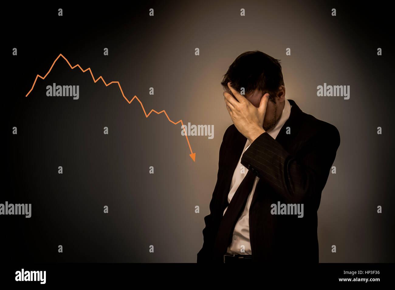 Singola business man in piedi da solo con la mano sul suo viso e con la caduta di grafico Immagini Stock