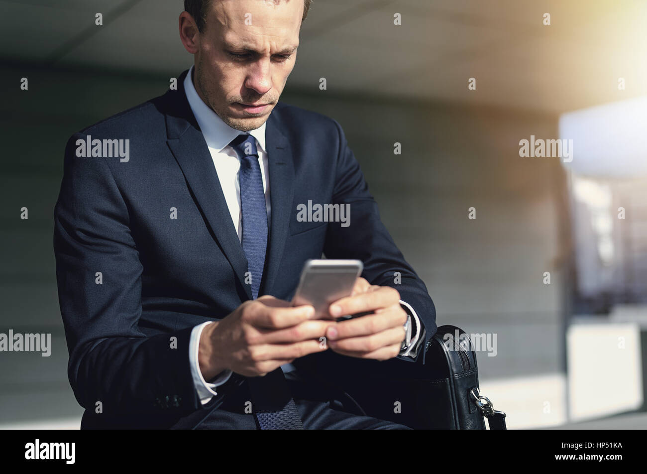 Fiducioso bello imprenditore utilizzando il suo telefono. Interni orizzontali shot Immagini Stock
