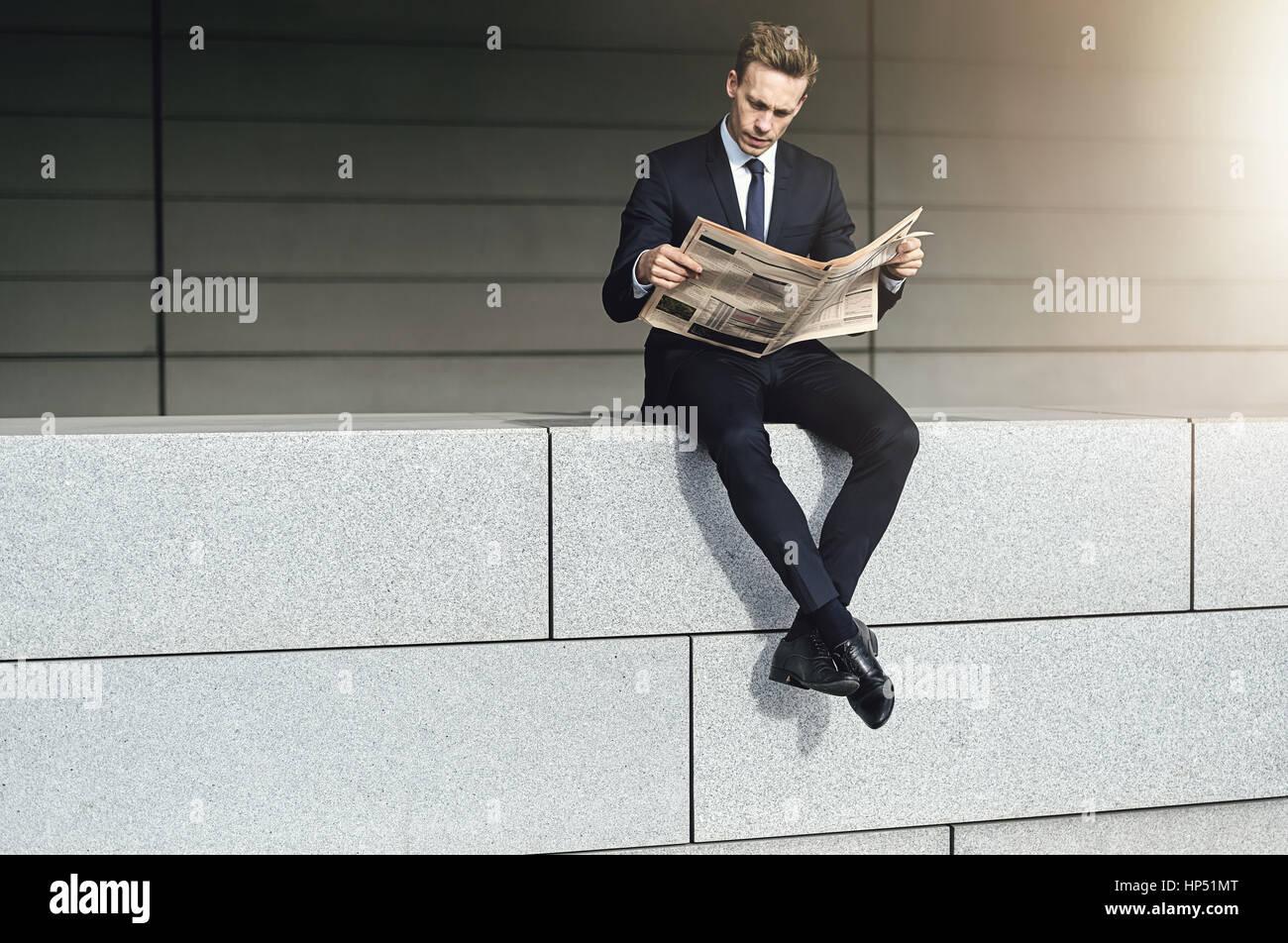 Cool imprenditore siede su un muro di mattoni con quotidiano Immagini Stock