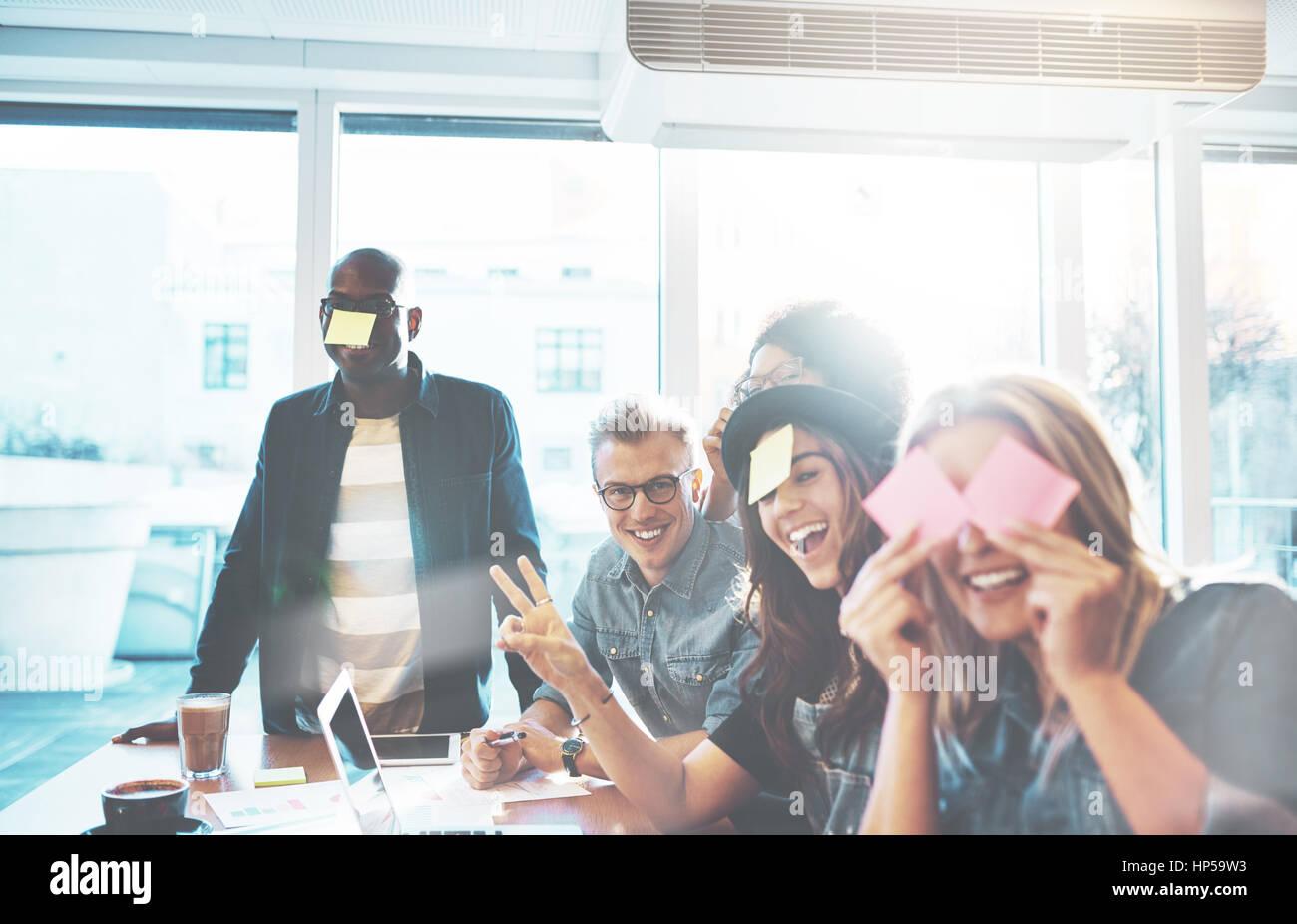 Bella giovani si divertono con sticky notes seduti insieme al tavolo del bar vicino alla finestra luminosa, giocando Immagini Stock