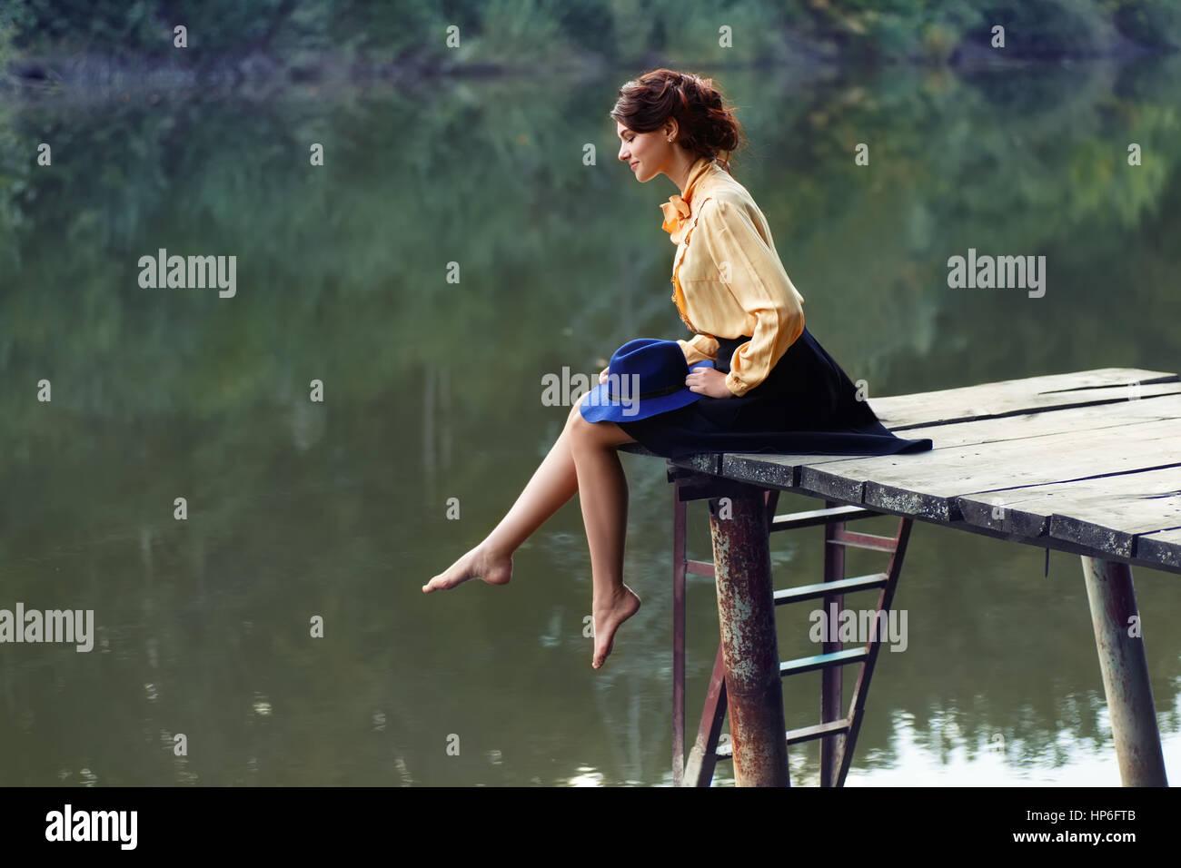 Vista Laterale Del Sognare Ragazza Seduta Sul Molo La Foresta E Il Fiume Sullo Sfondo Bella Donna Seduta Dal Lago Lonely Donna Seduta Su Una Tavola Di Legno Brid Foto Stock