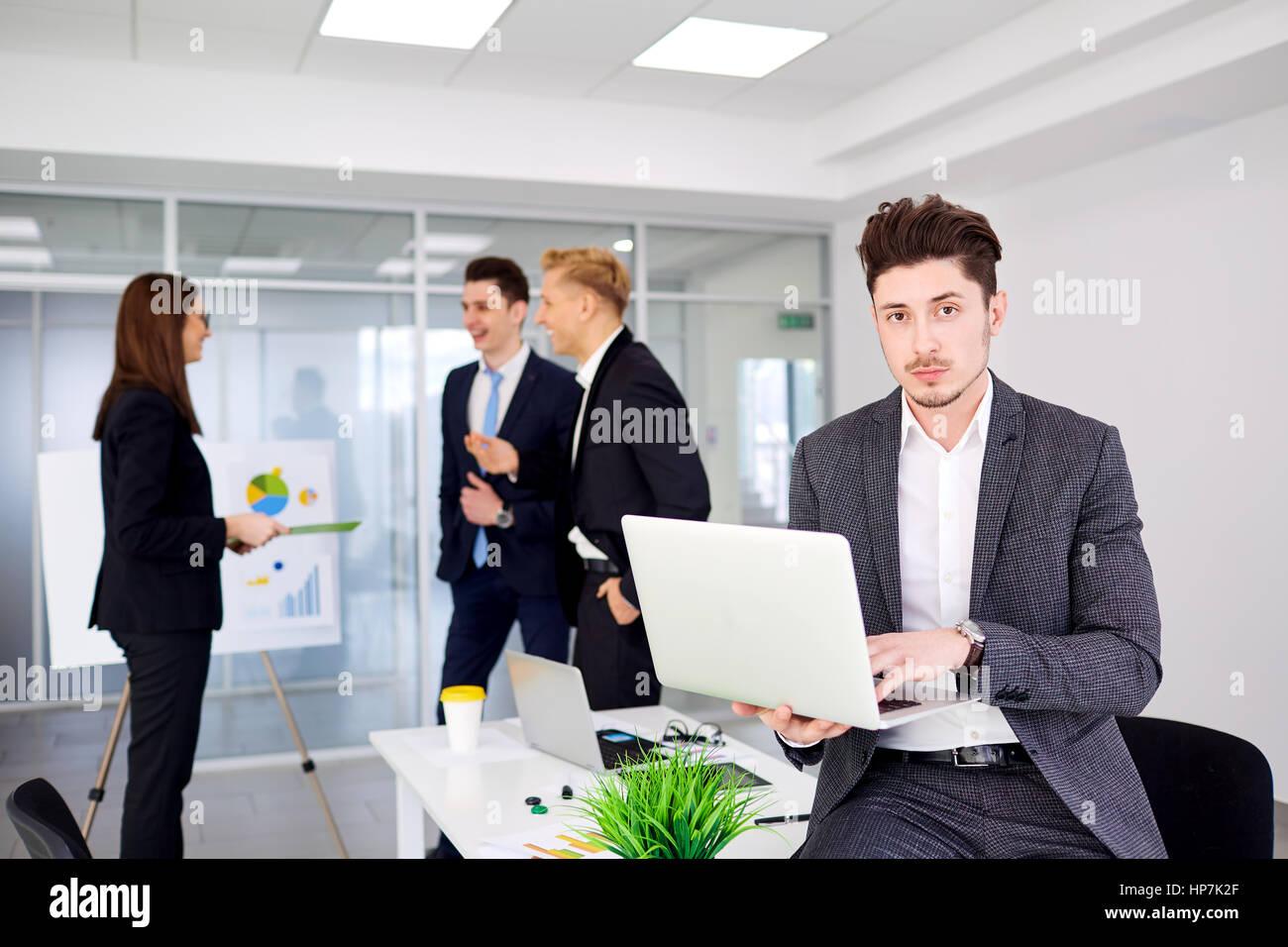 Giovane imprenditore con un laptop nelle mani di opere in backgr Immagini Stock