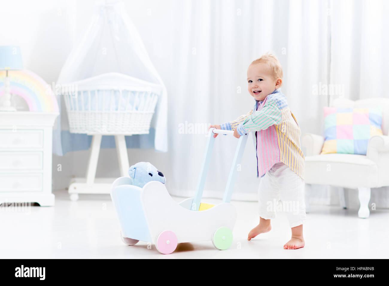 Bambino ad imparare a camminare con spinta in legno walker in camera da letto bianco pastello con colore arcobaleno Immagini Stock