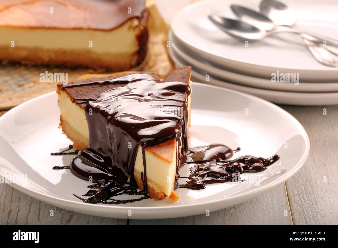 Cheesecake fetta con il cioccolato fuso Immagini Stock