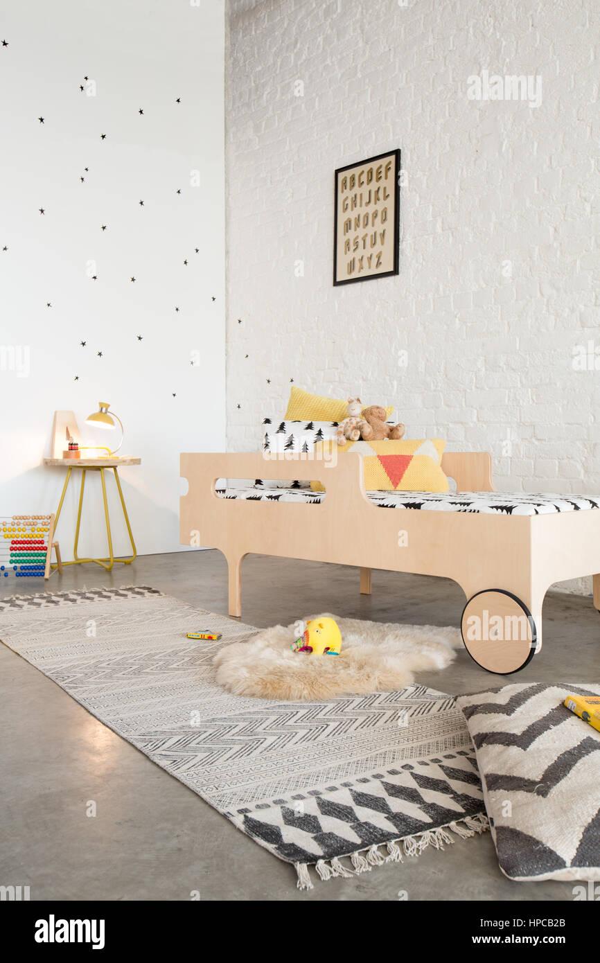 Un letto del bambino in una camera da letto con pareti bianche e pavimento di calcestruzzo colato Foto Stock