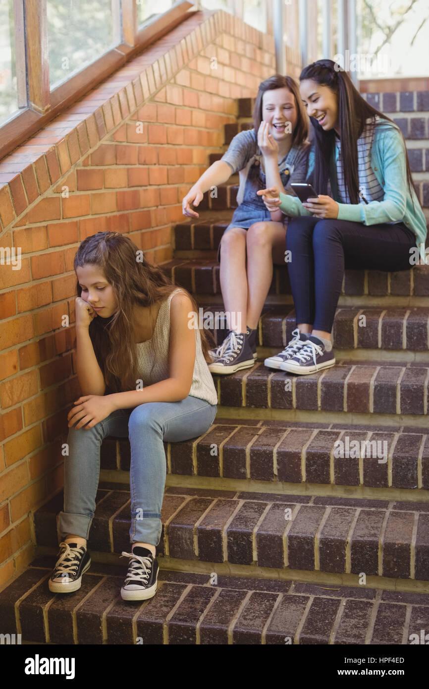 Amici di scuola bullismo una ragazza triste nel corridoio della scuola a scuola Immagini Stock