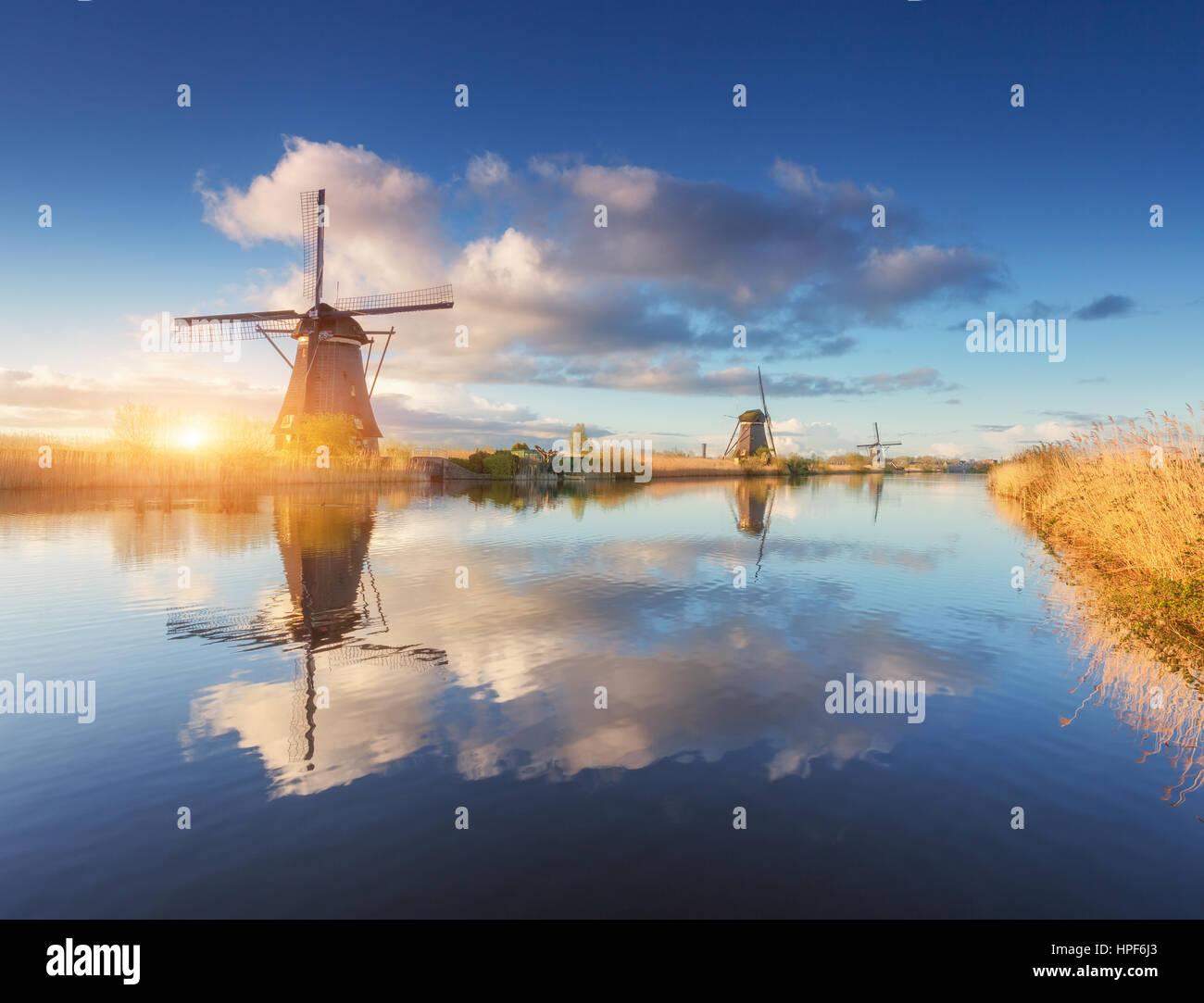 Mulini a vento di sunrise. Paesaggio agreste con sorprendente olandese di mulini a vento in prossimità dell'acqua Immagini Stock