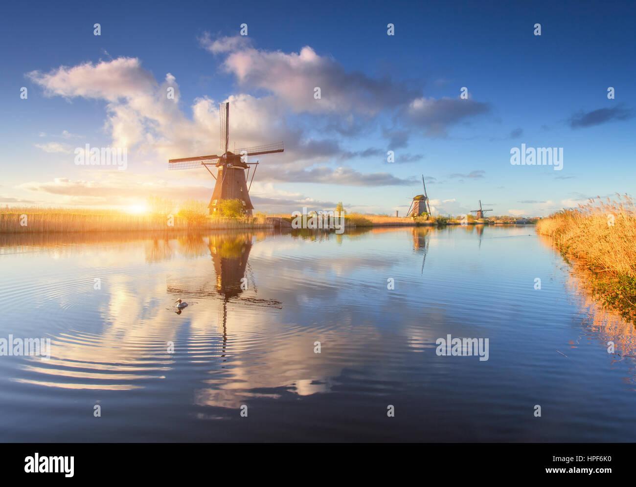 Mulini a vento di sunrise. Paesaggio agreste con sorprendente olandese di mulini a vento in prossimità dell'acqua Foto Stock