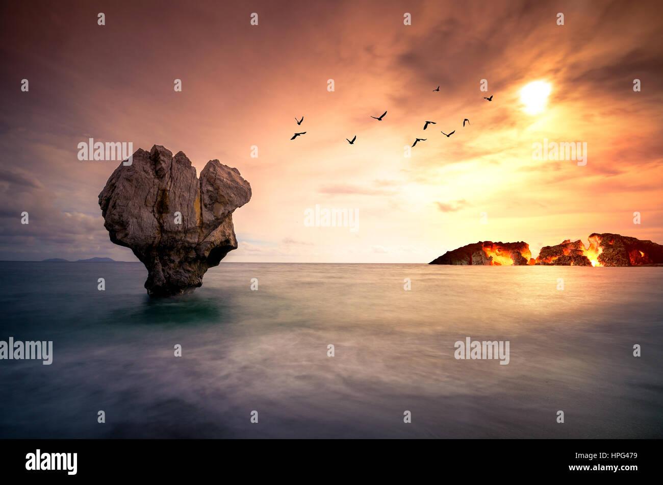 Arte con lonely scultura in pietra nel mare con sagome di uccelli in volo e un'isola che brucia sotto il tramonto. Immagini Stock