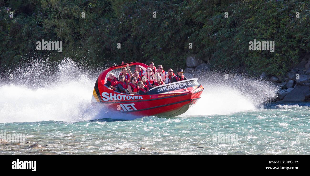 Queenstown, Otago, Nuova Zelanda. Shotover Jet Boat accelerando attraverso le acque turchesi e cristalline del fiume Immagini Stock