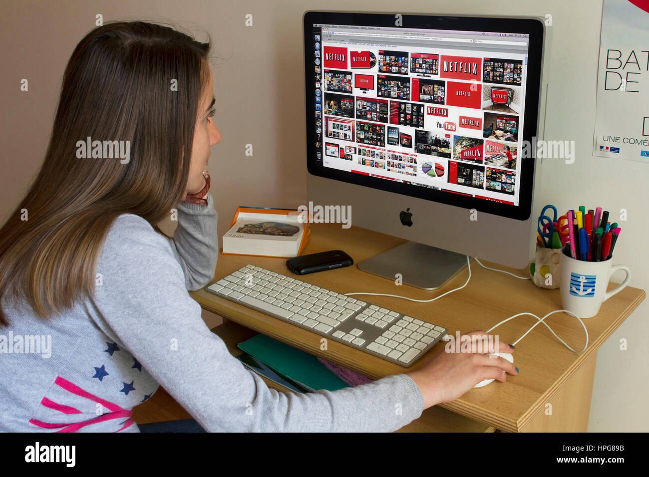 Schoolgirl davanti allo schermo di un computer la visualizzazione di Netflix. Immagini Stock