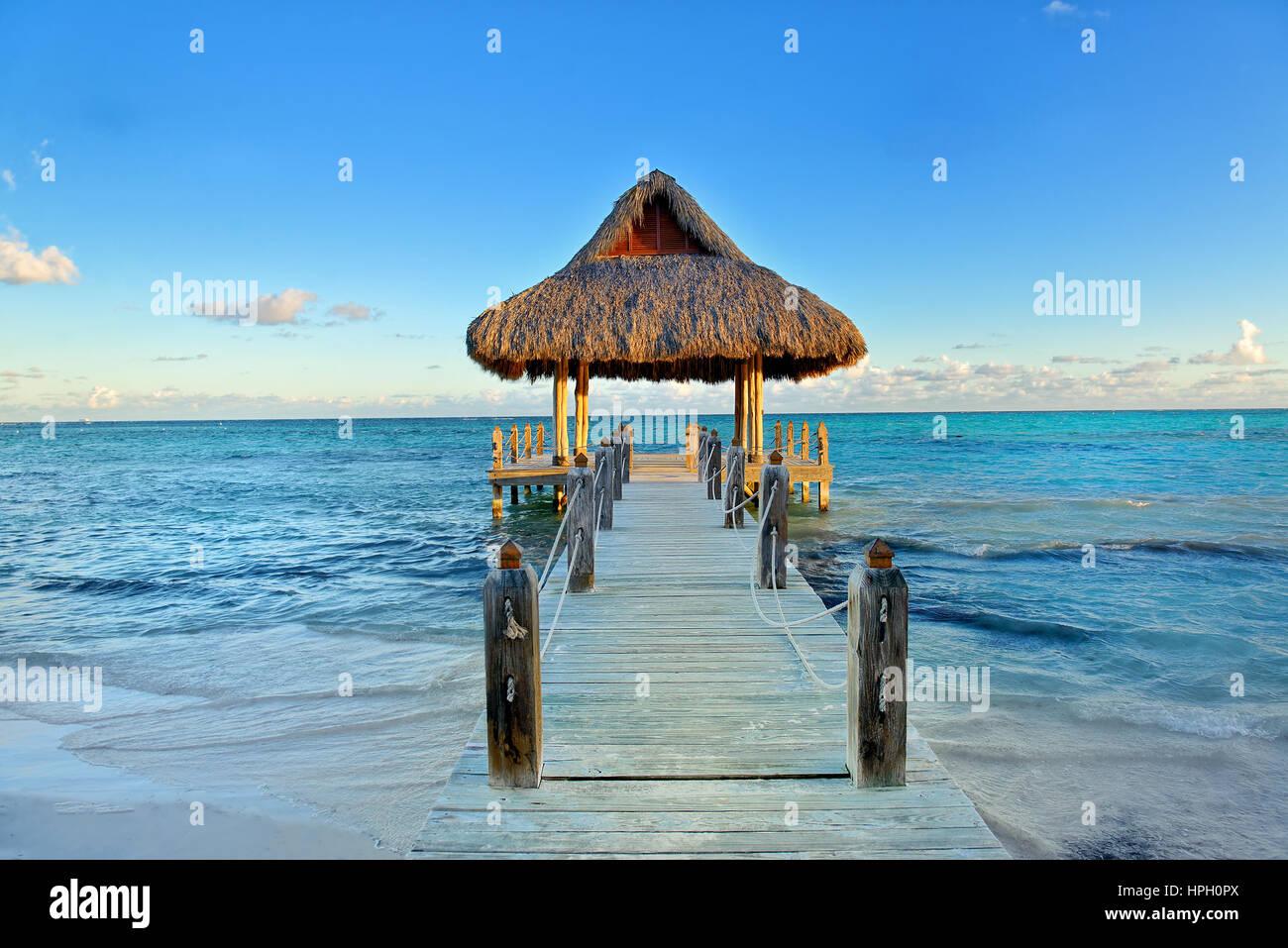 Tropical spiaggia di sabbia bianca. Di foglie di palma di legno coperto pier con gazebo sulla spiaggia. Punta Cana, Immagini Stock