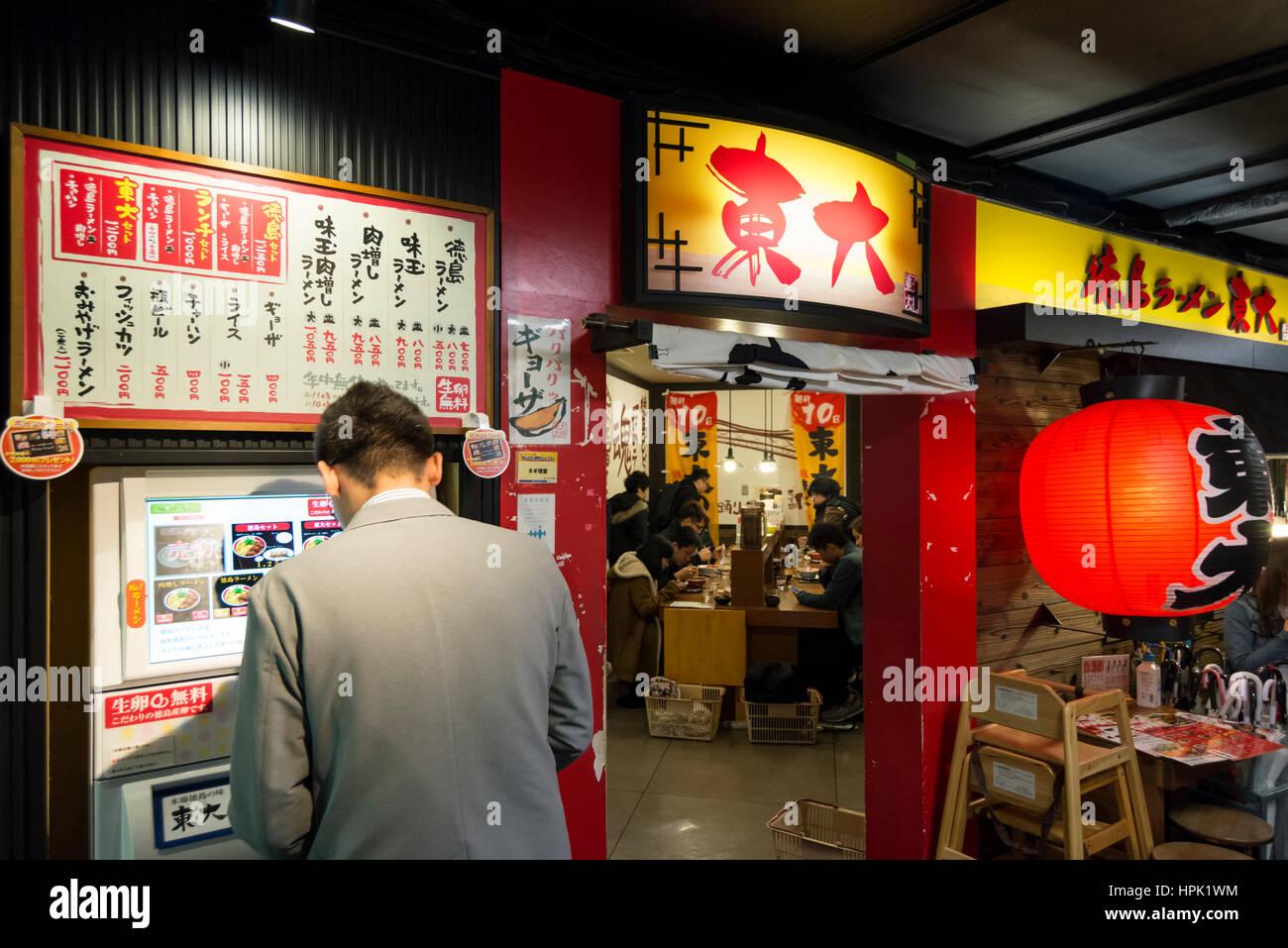 Un uomo di pagare per il cibo in anticipo presso un distributore automatico al di fuori di un ristorante prima di Immagini Stock
