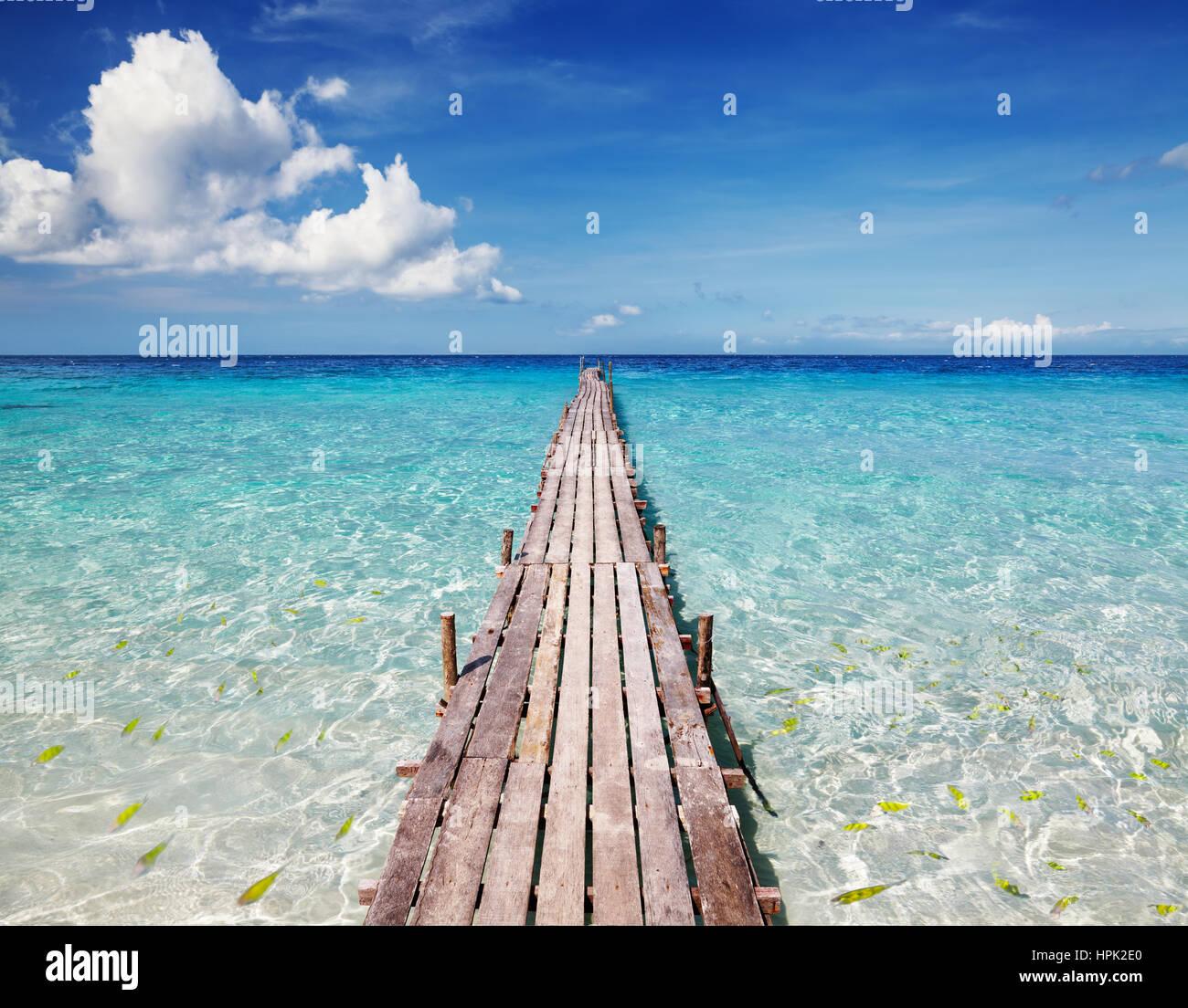 Il molo di legno su un isola tropicale, un mare limpido e azzurro del cielo Immagini Stock