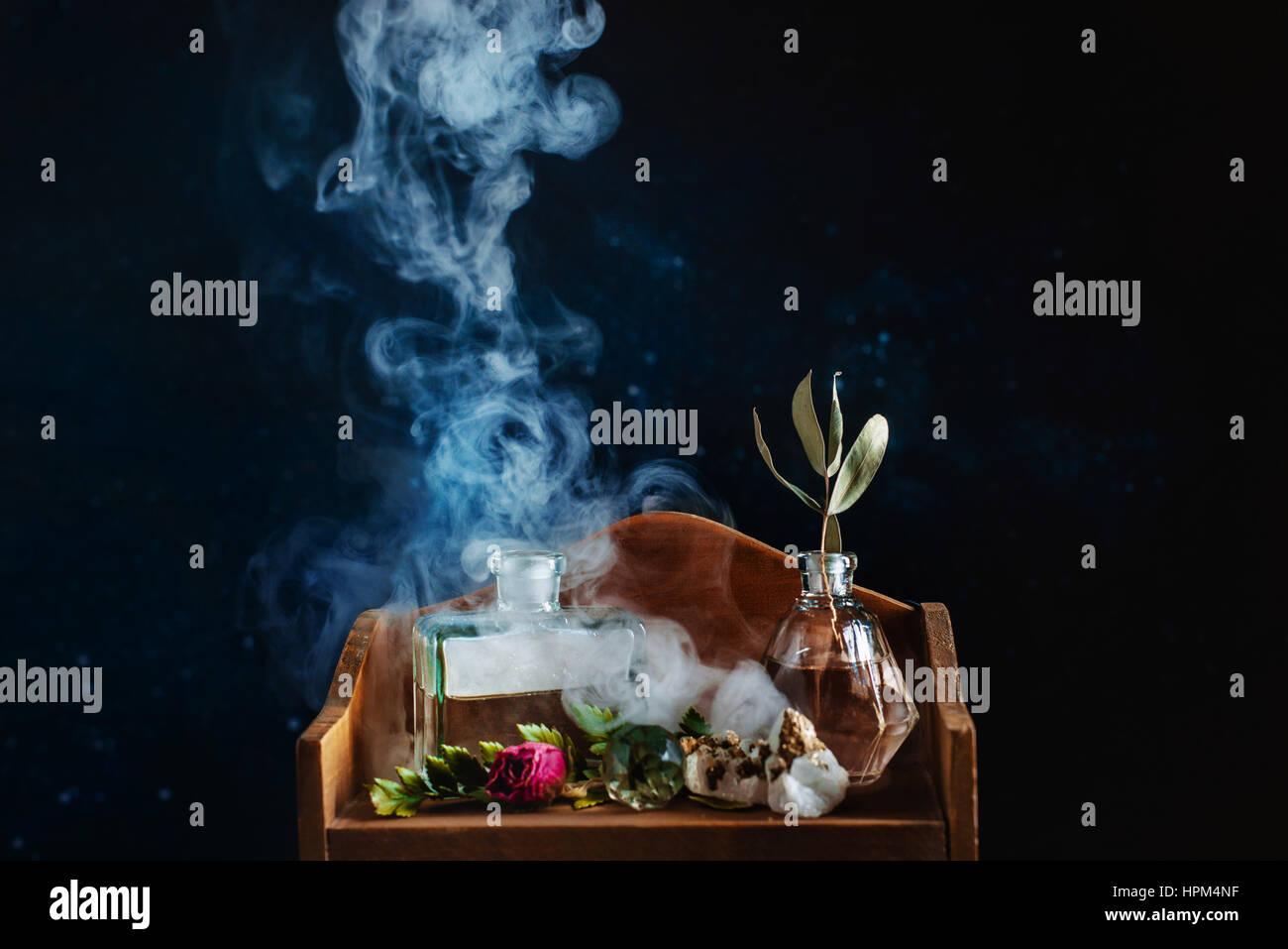 Ripiano in legno con le bottiglie di vetro, pietre, foglie e con l'aumento del fumo su sfondo scuro Immagini Stock