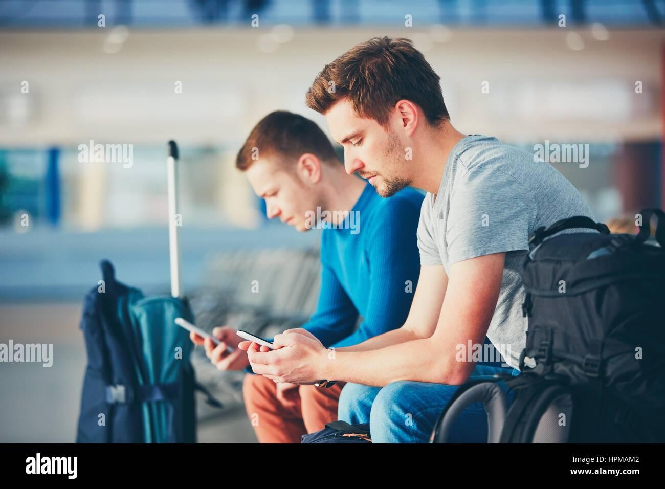 Due amici che viaggiano insieme. I viaggiatori con i telefoni cellulari di attesa in aeroporto area di partenza Immagini Stock