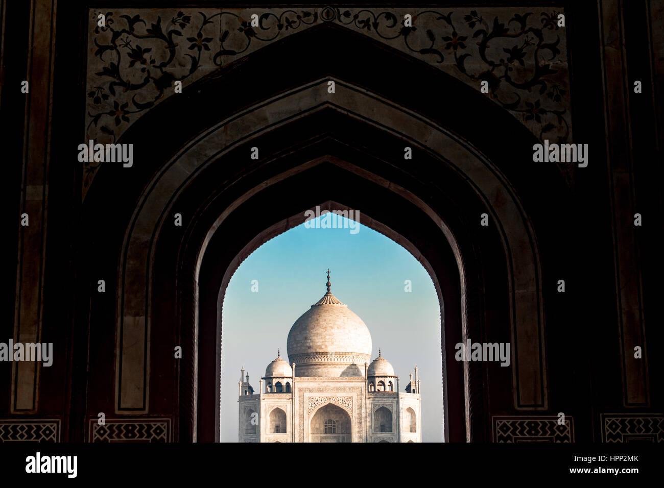 Punto di vista lontano del Taj Mahal dietro cancelli ingresso archi Immagini Stock