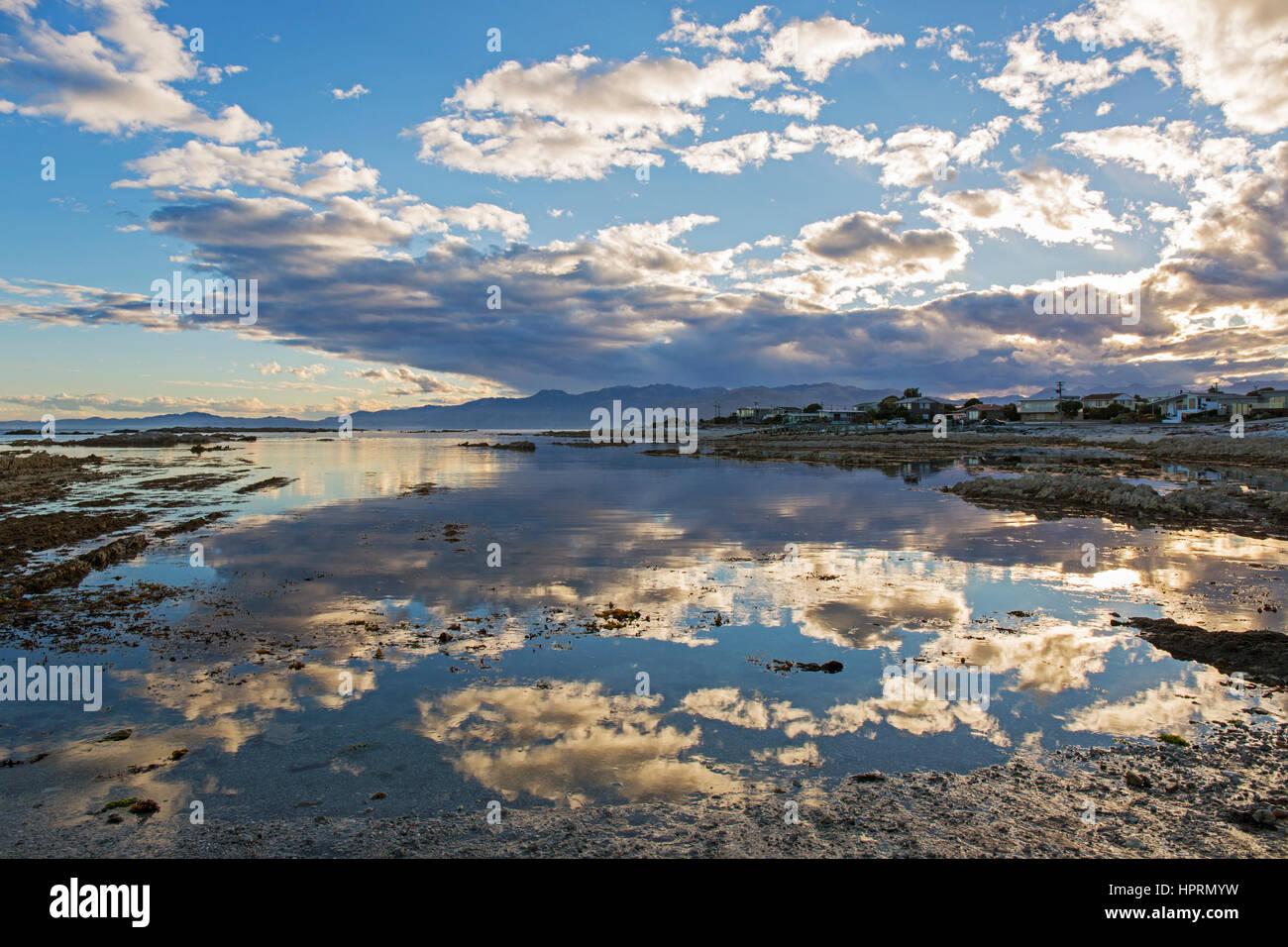 Kaikoura, Canterbury, Nuova Zelanda. Vista su tutta la baia del Sud a sera, cloud-riempito il cielo si riflette ancora in acqua. Foto Stock