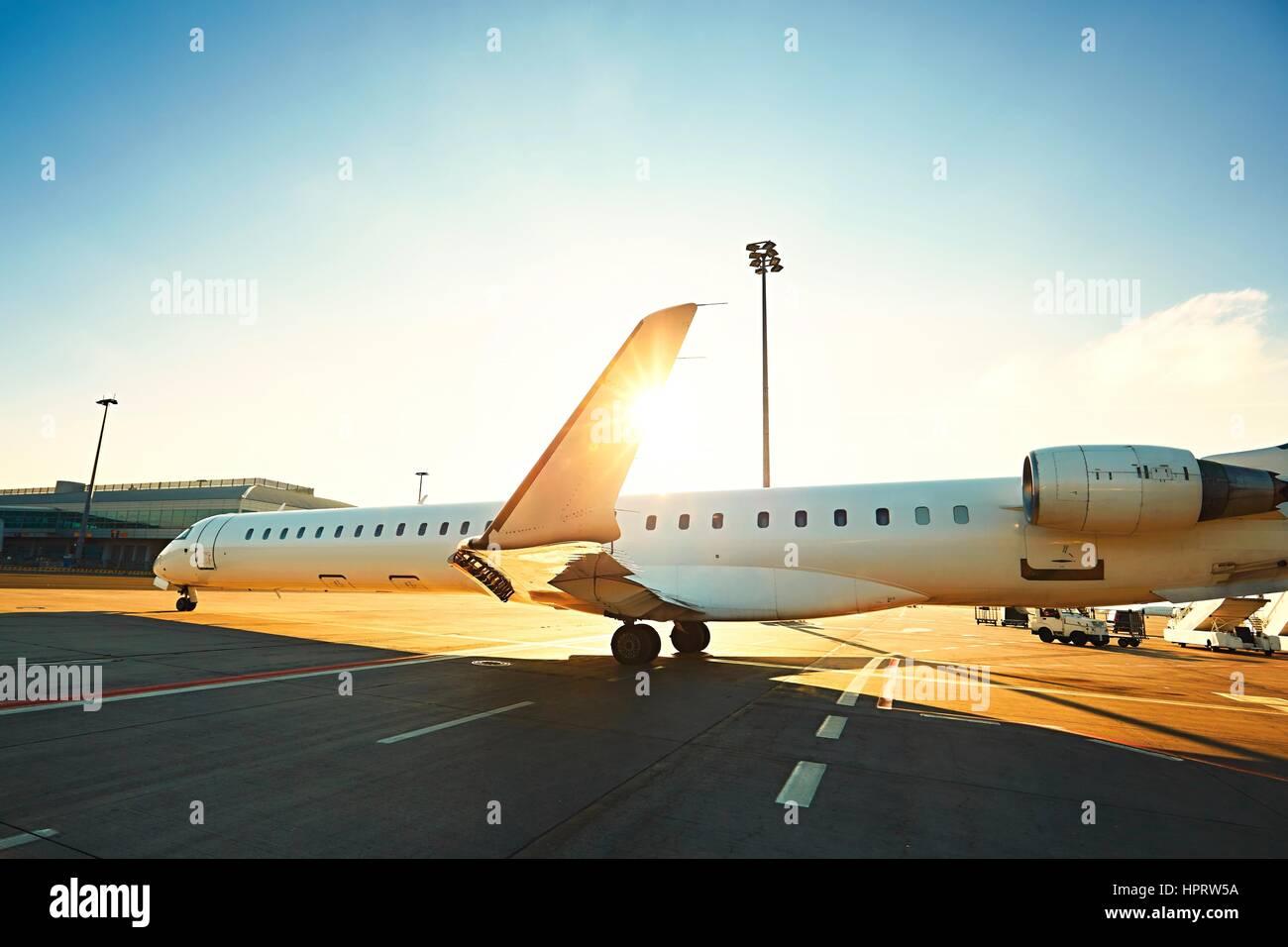 La vita quotidiana all'aeroporto internazionale. Il velivolo è il rullaggio in pista durante il tramonto. Immagini Stock