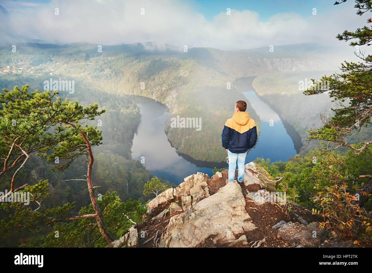 Traveler sulla sommità della roccia. Giovane uomo gode di vista sulla valle del fiume nella nebbia mattutina. Immagini Stock