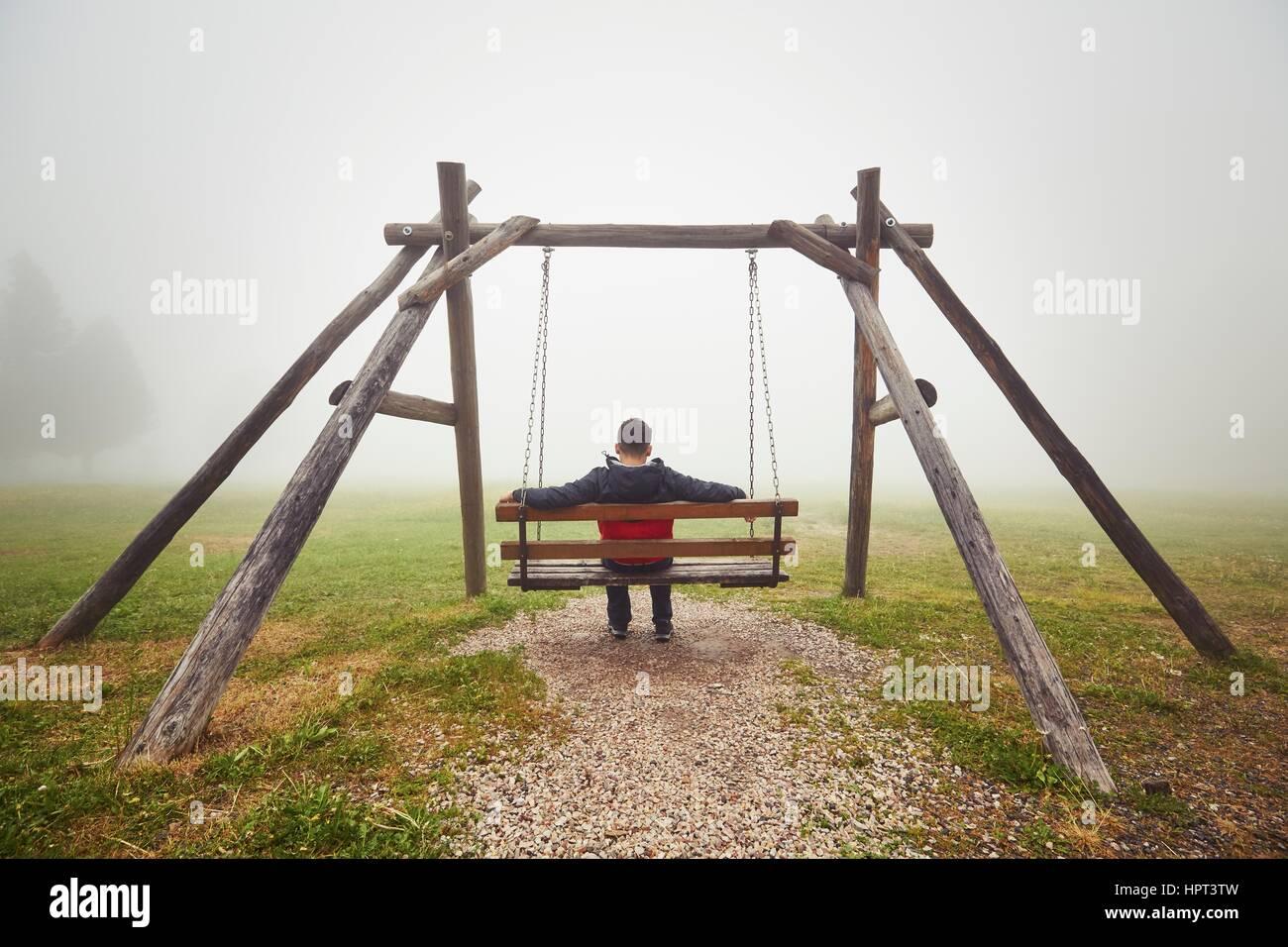 Triste uomo sull'altalena nella nebbia misteriosa Immagini Stock
