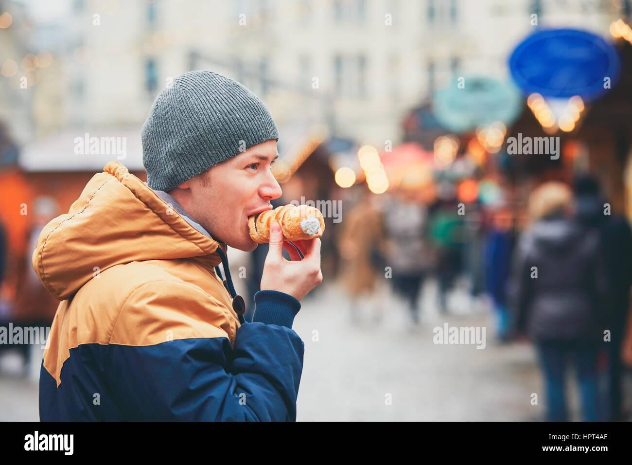 Giovane uomo mangiare pasta rotolo con crema di latte sul mercato di natale, Vienna, Austria Immagini Stock