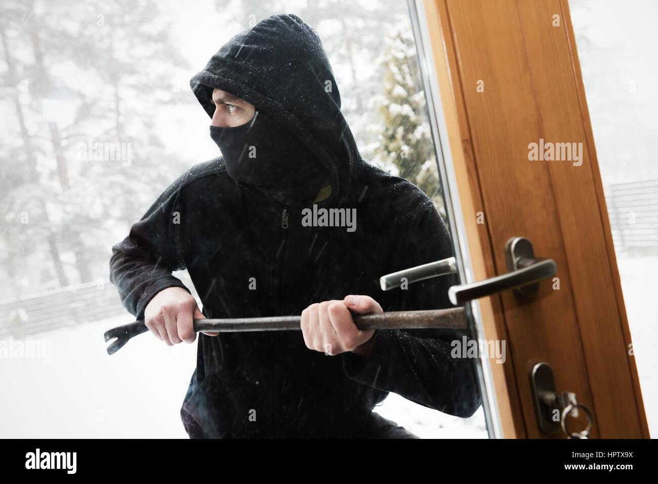 Rapina in casa - rapinatore cercando porta aperta con palanchino Foto Stock