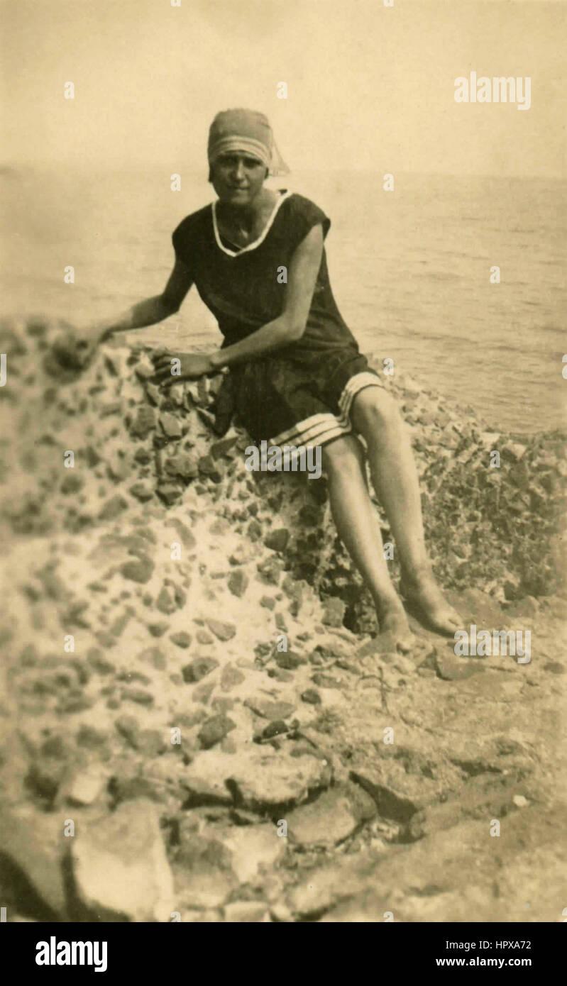 Una donna su una spiaggia rocciosa, Italia Immagini Stock