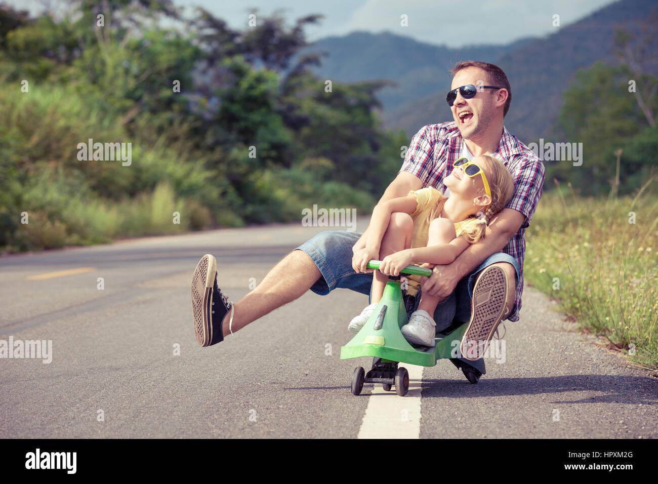 Padre e figlia giocando sulla strada al giorno. Concetto di famiglia amichevole. Foto Stock