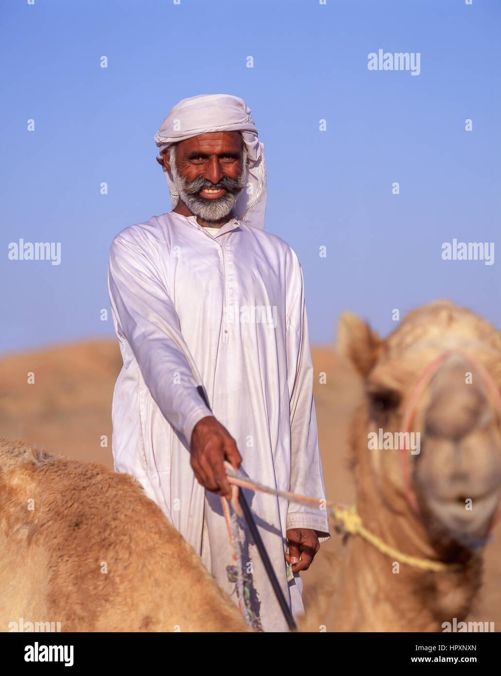 Sorridente camel driver con cammello nel deserto di Dubai, Dubai, Emirati Arabi Uniti Foto Stock