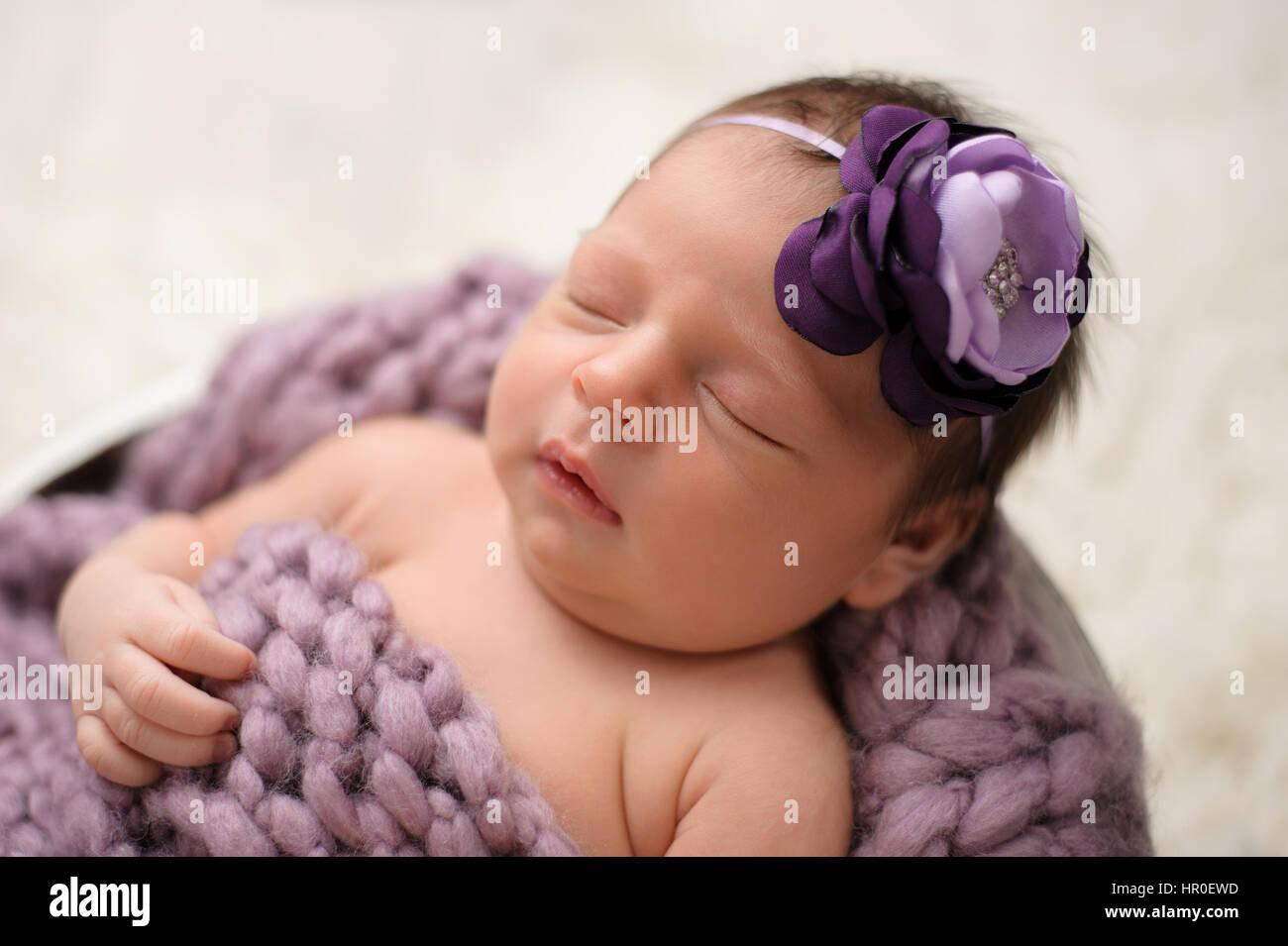4013e109cd Nove giorni di età neonato ragazza dorme in un secchio di legno. Indossa una  lavanda
