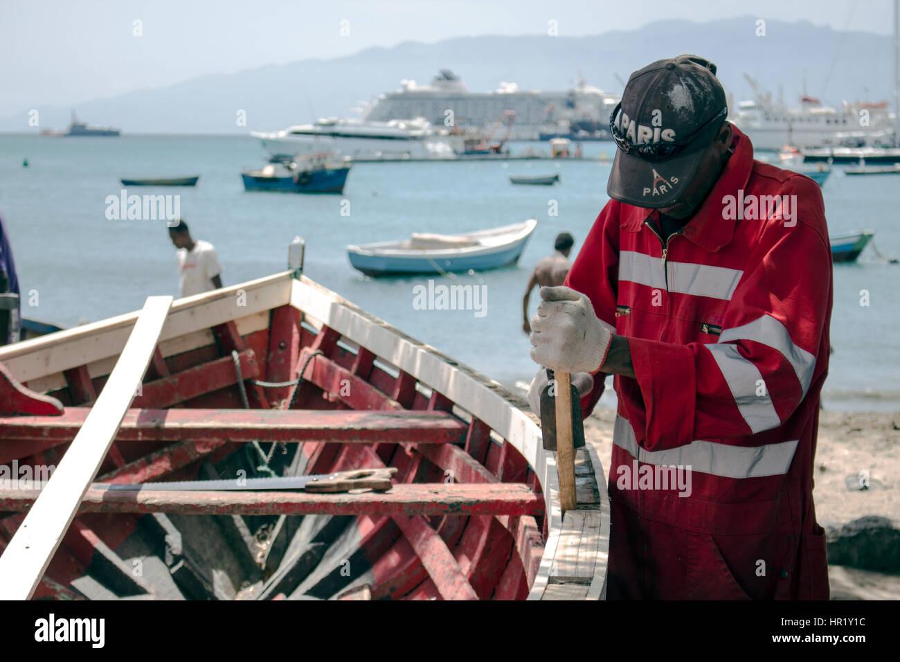 Un operaio falegname è la riparazione di una barca di legno nel complesso da indossare guanti e. Immagini Stock