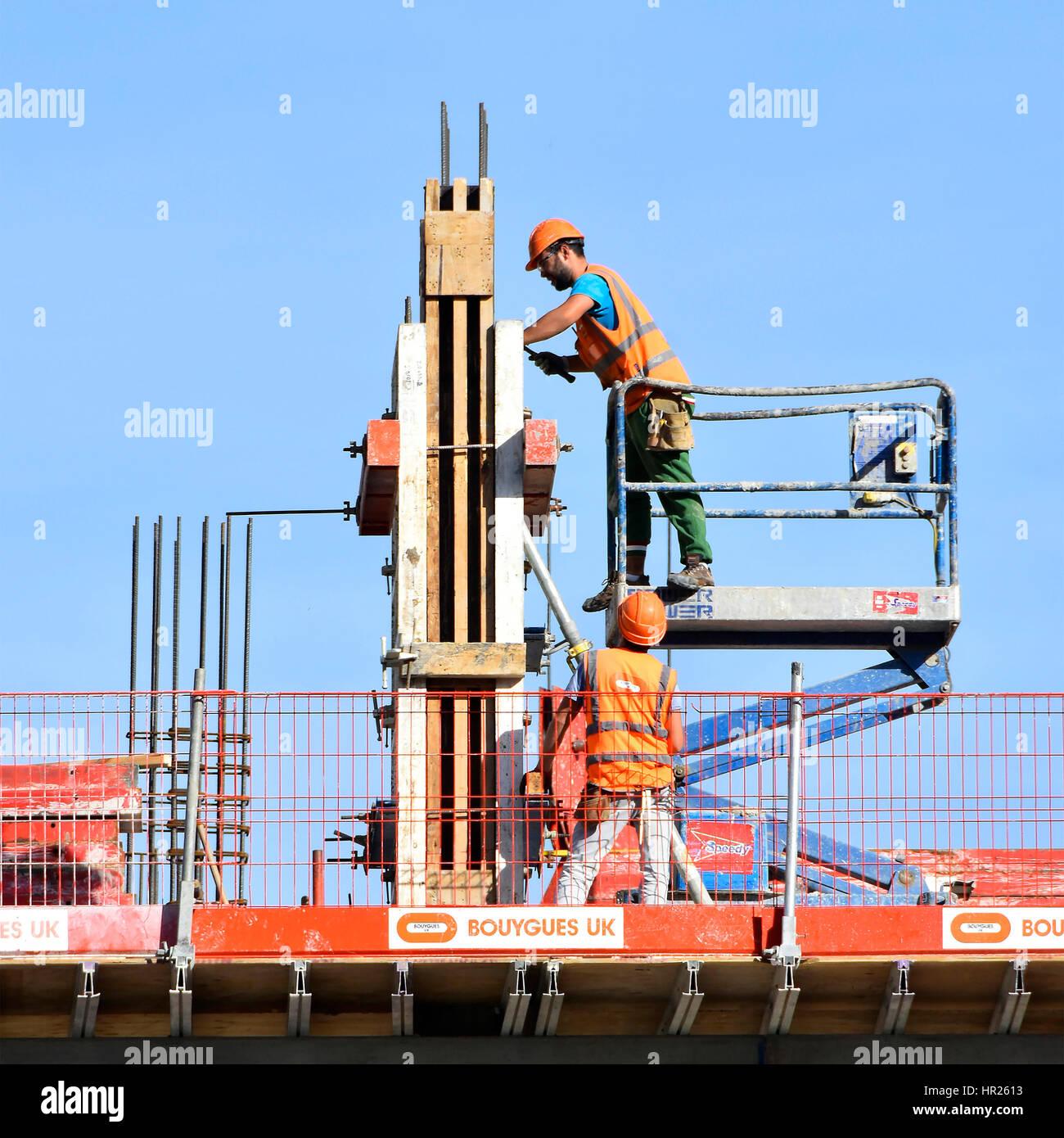Salute e sicurezza edificio sito in costruzione i lavoratori che fissa la colonna cassero lavorando insieme duro Immagini Stock
