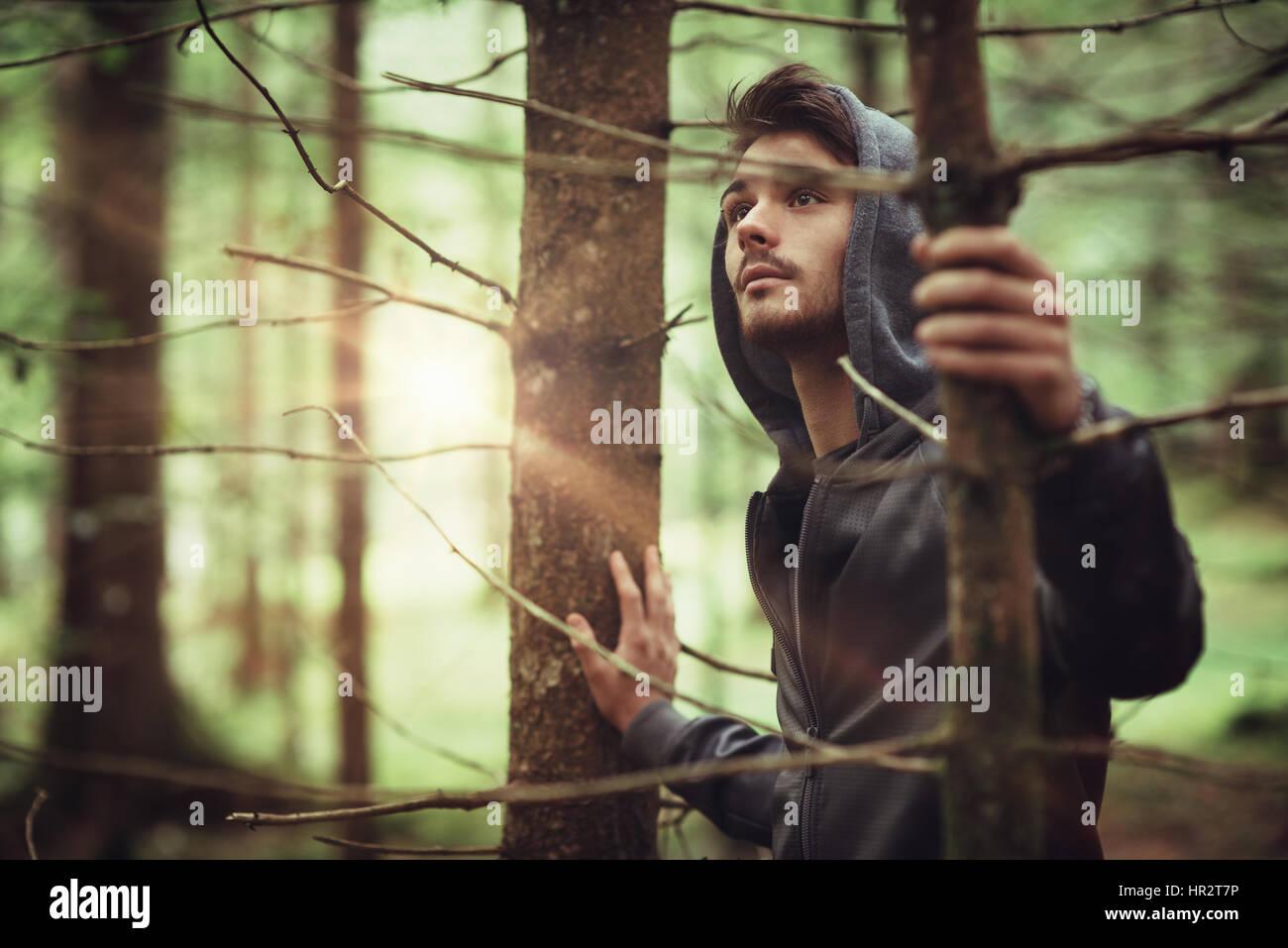 Ragazzo con cappuccio in boschi esplorando la natura, l'individualità e il concetto di libertà Immagini Stock