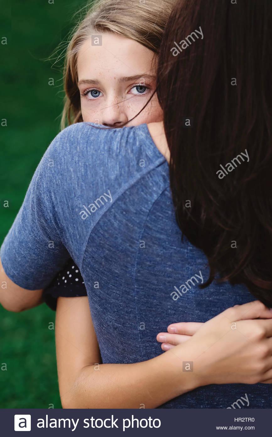 Figlia di madre che abbraccia e guardandosi le spalle Foto Stock